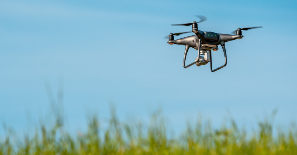 Drone quadcopter hovering over grass field on sunny day [Canva License]